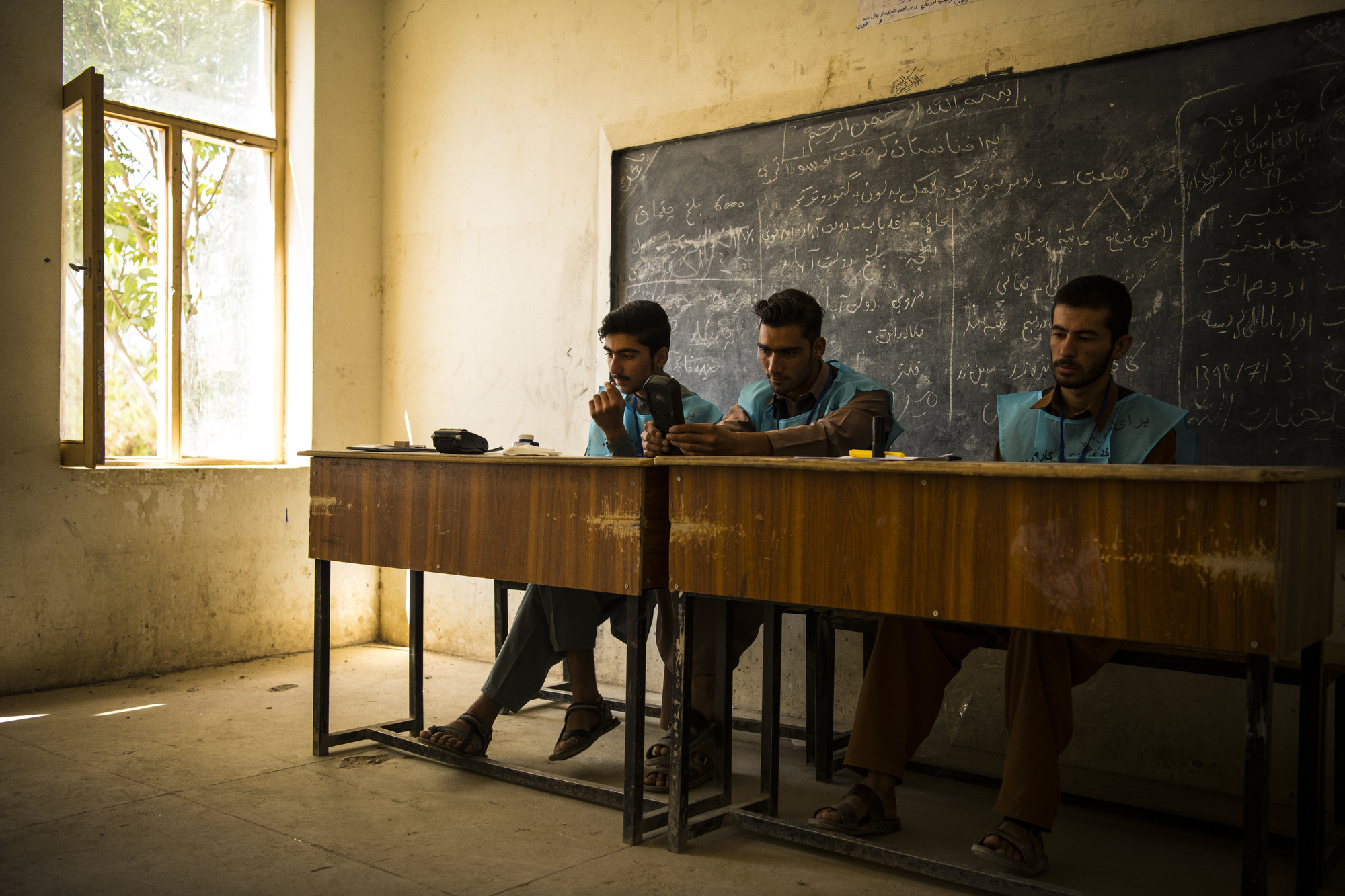 With intermittent fighting and rocket attacks throughout the day, election workers in the Awal Baba school voting centre in Maidan Shahr, had little work to do. Photo: Andrew Quilty, 2019.