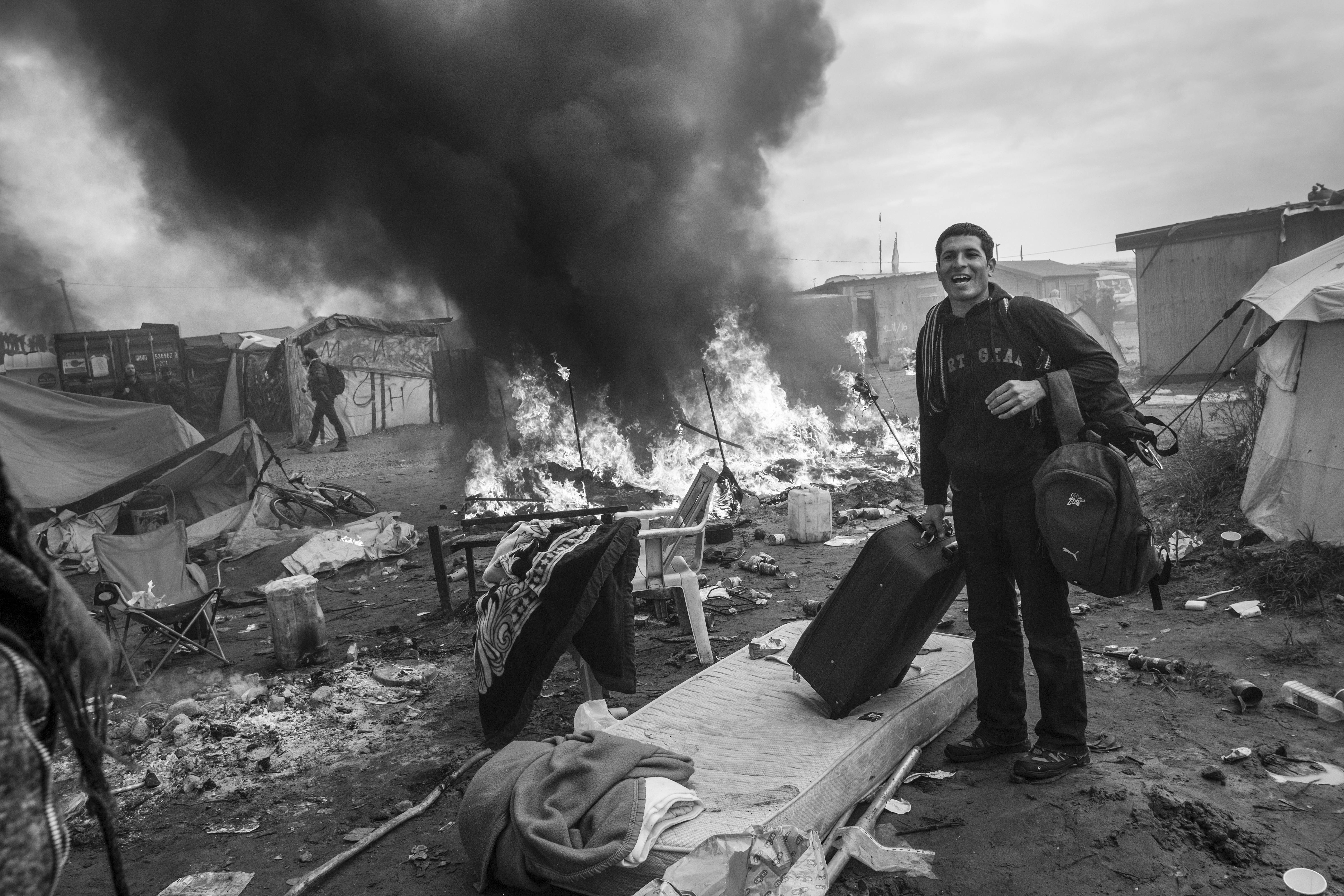 "An Afghan refugee packs his belongings while a fire destroys his tent in ""The Jungle"" on the third day of a police operation. The French authorities are trying to close and demolish the makeshift refugee camp next to the highway leading to the port of Calais. An estimated 8,000 refugees and migrants have been staying here, trying to reach the UK. (26 October 2016) - Photo: Joel van Houdt"
