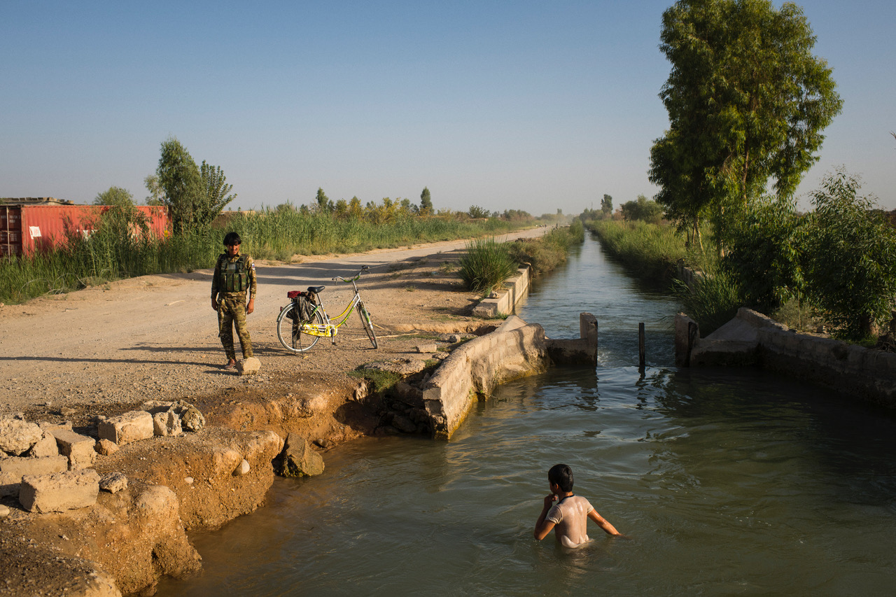 Boys cool off in the canal running through Nad Ali district centre: from mid-2015 to 2017, it marked an impassable frontline. Photo: Andrew Quilty, 2018.