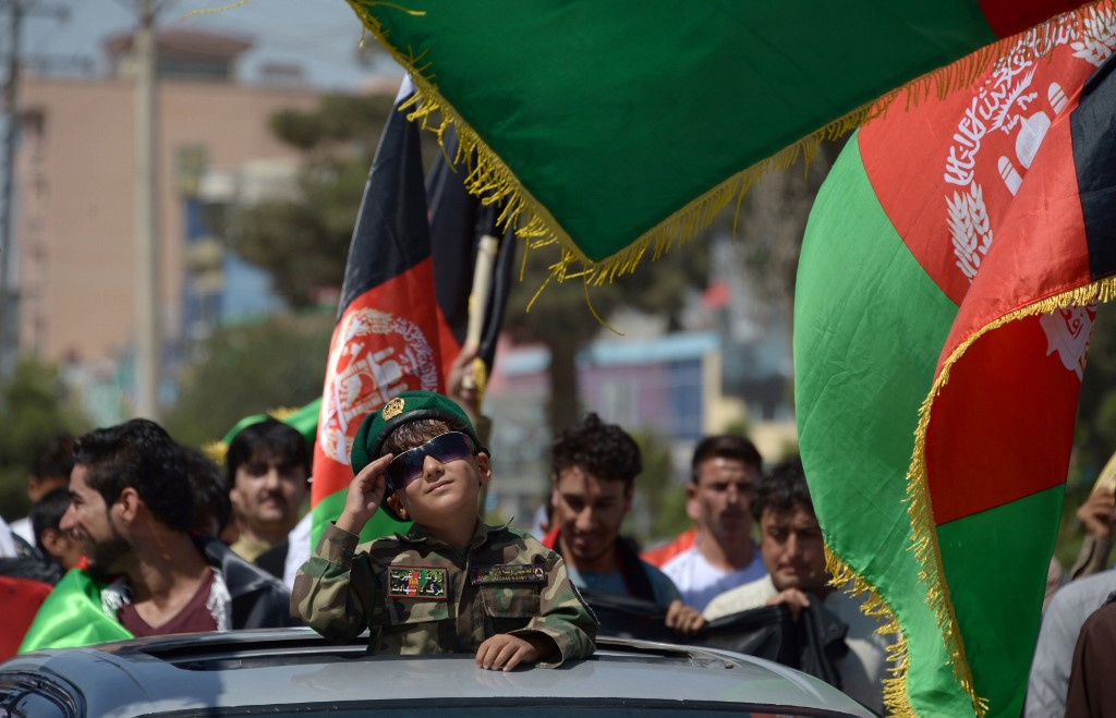 An Afghan boy salutes while dressed in military gear during celebrations to mark the country's independence day, Mazar-e Sharif, 2017. Photo: Farshad Usyan/AFP.