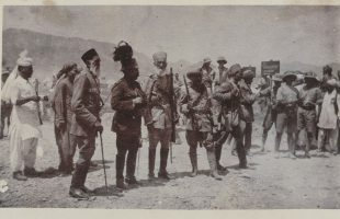 """The Afghan peace delegation while crossing the Torkham border on their way to the Rawalpindi peace conference, 24 July 1919. The tall, bearded man on the left is Ghulam Muhammad Khan Wardak, then Minister of Commerce, while the figure in the centre with a plumed cap is probably Mahmud Tarzi, Minister of Foreign Affairs and head of the delegation."""